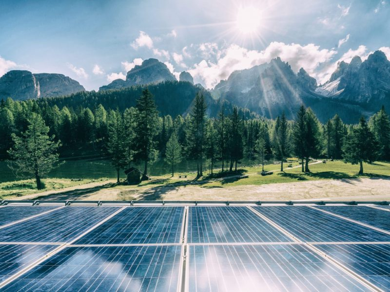 Solar cell panel in country landscape against sunny sky and mountain backgrounds. Solar power is the innovation for sustainability of world energy. Sustainable resources.